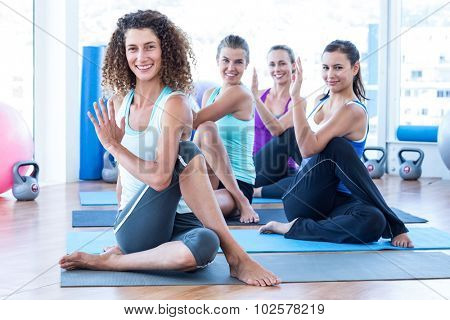 Portrait of cheerful women doing spine twisting pose on exercise mat