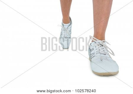 Low section of woman wearing sports shoe running over white background