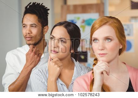 Thoughtful business people thinking with hands on chin and looking away at office