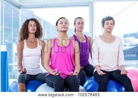 Women relaxing on exercise balls with eyes closed in fitness studio