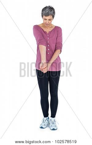 Mature woman stretching over white backgrounnd