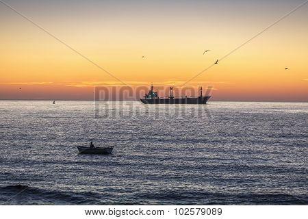 Cargo ship sailing on sunrise near the sea harbor