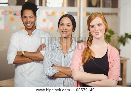 Portrait of smiling business people with arms crossed in office