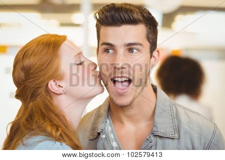 Woman kissing shocked businessman in creative office