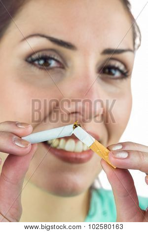 Close-up portrait of happy woman holding cigarette against white background