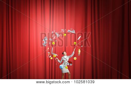 Young businesswoman in cap on stage juggling with icons