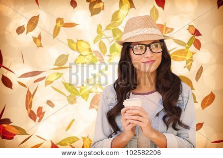 Brunette with disposable cup against autumnal leaf pattern in warm tones