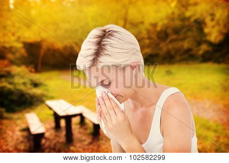 Sick woman blowing her nose against peaceful autumn scene in forest