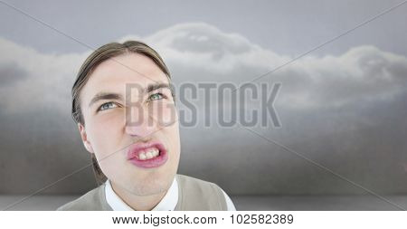 Geeky hipster grimacing against clouds in a room