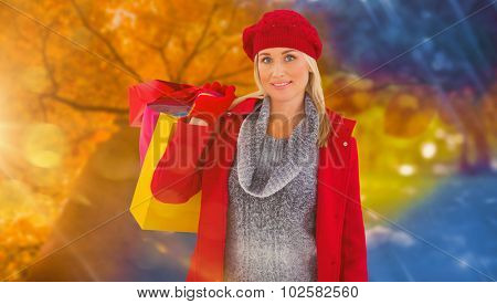 Blonde in winter clothes holding shopping bags against autumn changing to winter