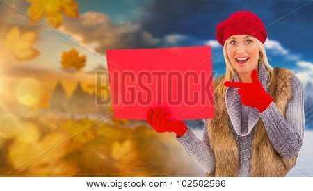 Blonde in winter clothes holding red sign against autumn changing to winter