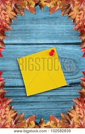 Digital image of pushpin on yellow paper against autumn leaves pattern