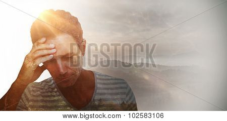 Upset man with hand on forehead against trees and mountain range against cloudy sky