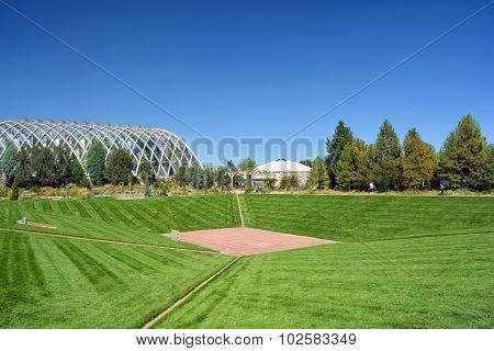 Retro Futuristic Greenhouse by a Grass Lawn Valley