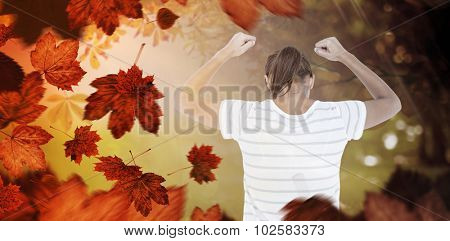 Depressed woman with hands raised against autumn scene