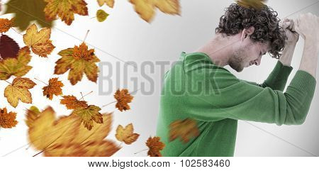 Depressed man over white background against autumn leaves