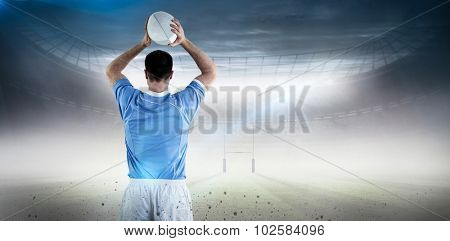 Rugby player about to throw a rugby ball against rugby pitch