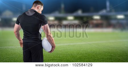 Tough rugby player holding ball against pitch and stands