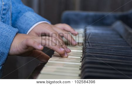 Child playing piano with selective focus and shallow depth of field.