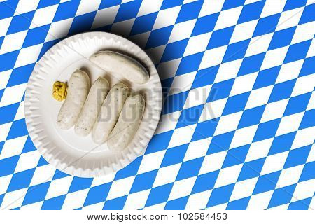 Traditional Bavarian Sausages On White Plate And Bavarian Flag