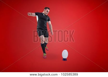 Rugby player kicking the ball against red background