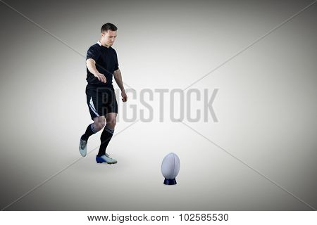 Rugby player doing a drop kick against grey vignette