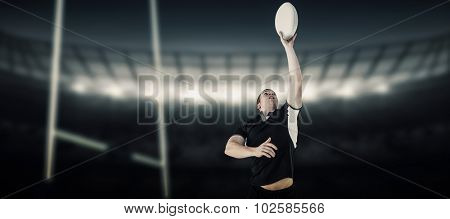Rugby player catching a rugby ball against rugby stadium