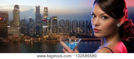 party, drinks, holidays, luxury and celebration concept - woman holding cocktail over singapore night city background
