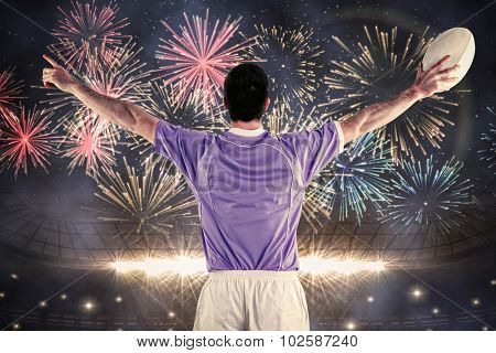 Rugby player gesturing with hands against fireworks exploding over football stadium
