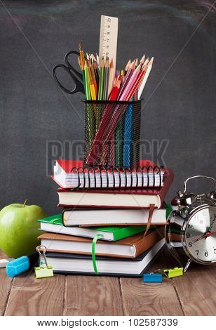School and office supplies on classroom table in front of blackboard
