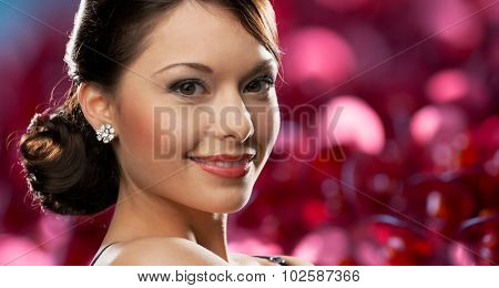 people, holidays, jewelry and luxury concept - smiling woman face with diamond earring over red lights background
