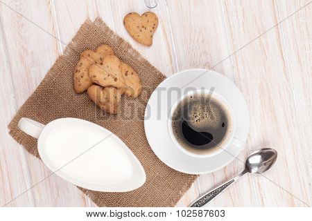 Coffee cup, heart shaped gingerbread cookies and milk pitcher. On white wooden table
