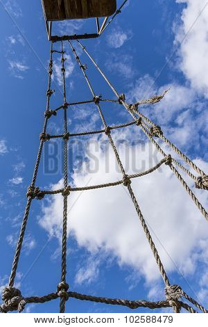 Old rope ladder against cloudy sky