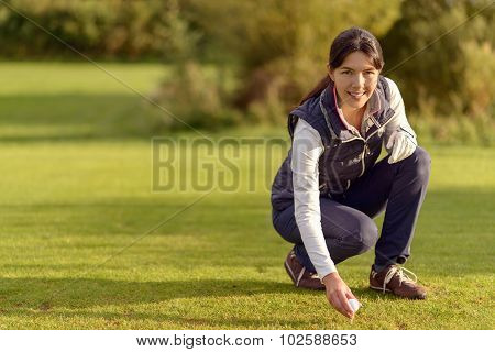 Smiling Female Golfer Placing A Ball On A Tee