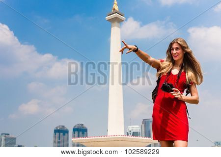 Woman photographing while sightseeing at national monument in Jakarta, Indonesia