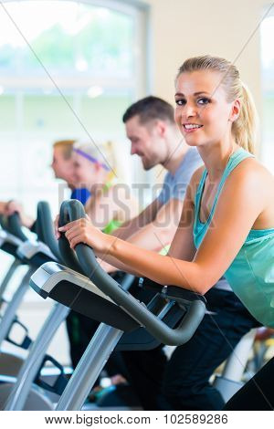 Group of fitness people in sport gym spinning on bicycles