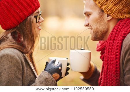 Amorous young couple having tea outdoors