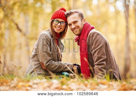 Amorous young couple relaxing in park in autumn