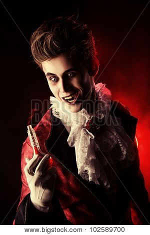 Frightening vampire holding youth elixir. Halloween. Dracula costume.