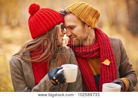 Amorous young couple in stylish casualwear holding cups of tea