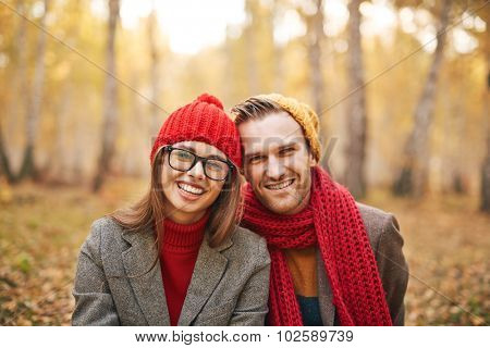 Stylish sweethearts in casualwear looking at camera in park