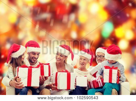 family, happiness, generation, holidays and people concept - happy family in santa helper hats with gift boxes sitting on couch over red lights background