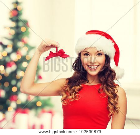christmas, x-mas, winter, happiness concept - smiling woman in santa helper hat with jingle bells