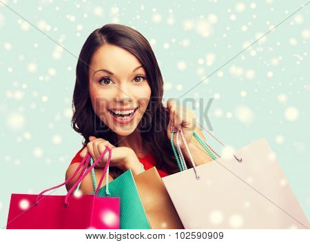 shopping, sale, gifts, christmas, x-mas concept - smiling woman in red dress with shopping bags