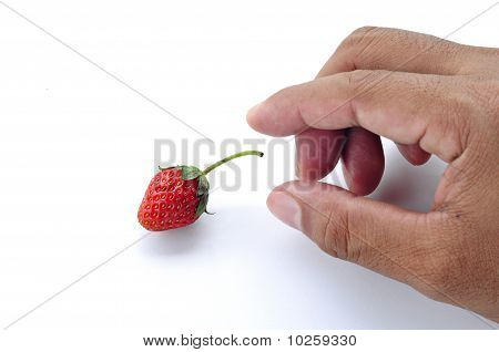hand try to pick a strawberry