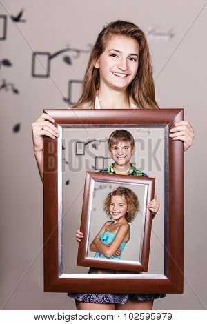 Happy sister holding portrait with her family