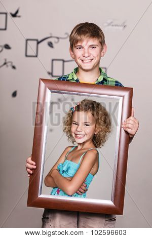Happy brother holding portrait with his sister