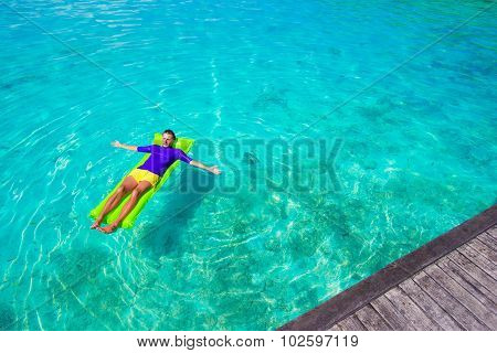 Young happy man relaxing on inflatable mattress in the sea