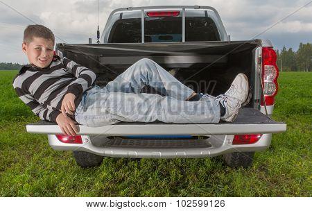 boy laying on car trunk