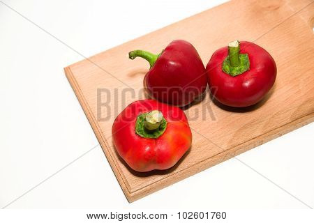 Three Ripe Red Peppers On Over White